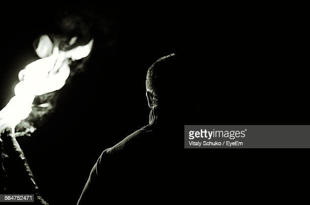 Rear View Of Man Holding Flaming Torch