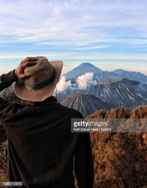 Rear View Of Man Holding Hat Against Mountains