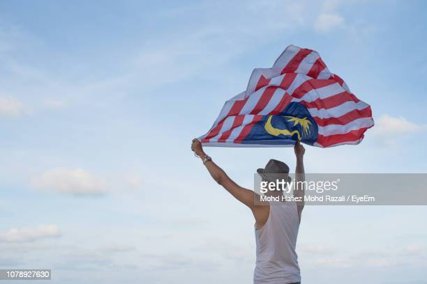 rear view of man holding malaysian flag against sky - 独立 ストックフォトと画像