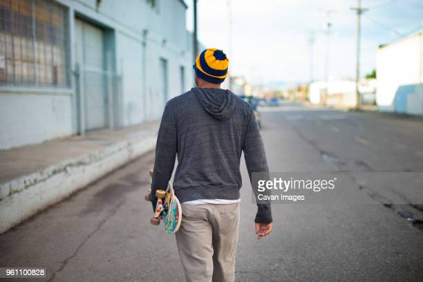 Rear view of man holding skateboard and walking on street