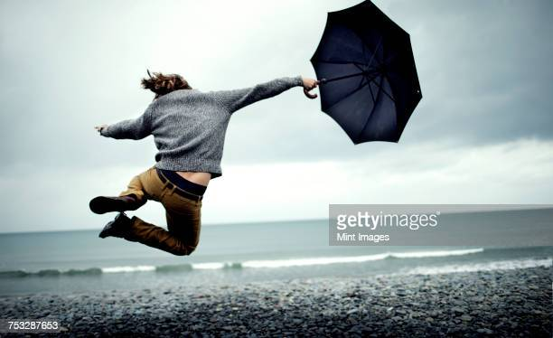 Rear view of man holding umbrella, jumping on beach by ocean, mid air.