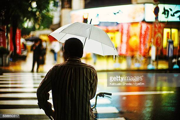 Rear View Of Man Holding Umbrella On Bicycle At Wet City Street