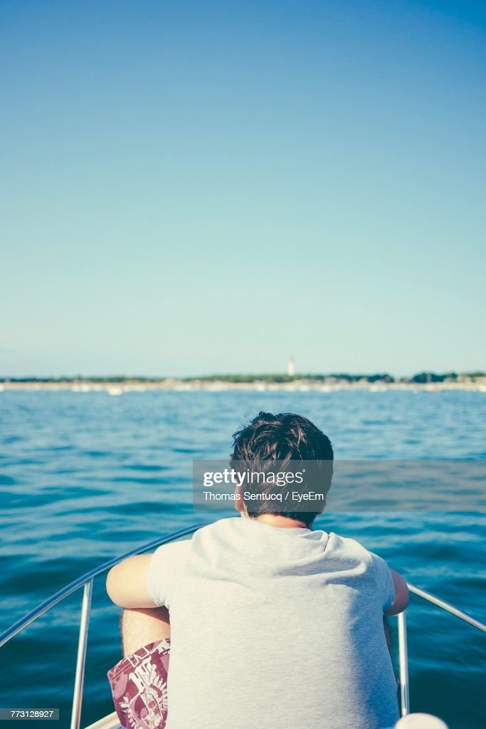 Rear View Of Man In Boat Against Clear Sky : Photo