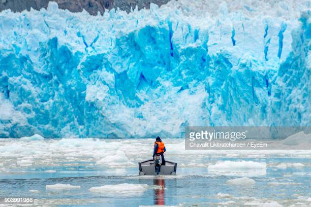 rear view of man in boat on frozen sea - patagonia chile stock photos and pictures