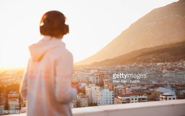 rear view of man in city against clear sky - hoodie headphones stock pictures, royalty-free photos & images