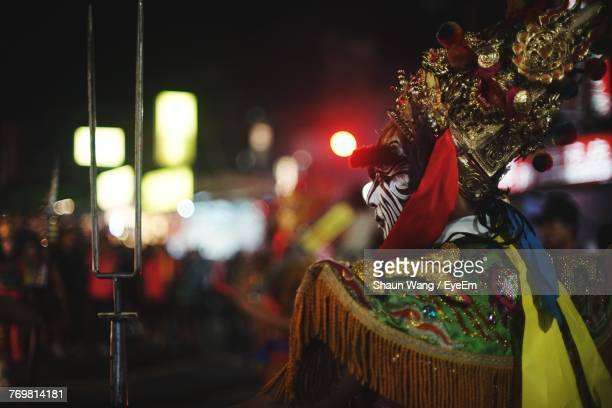 Rear View Of Man In Costume During Carnival At Night