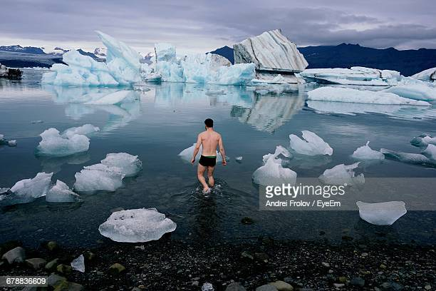 rear view of man in frozen water - halbbekleidet stock-fotos und bilder