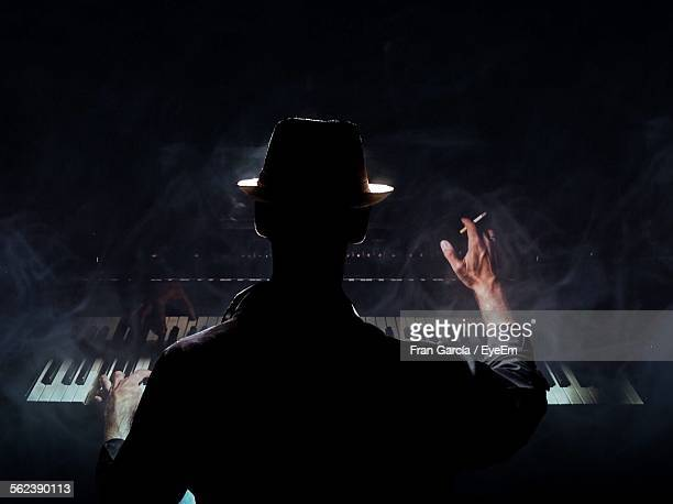 Rear View Of Man In Hat With Cigarette Playing Piano