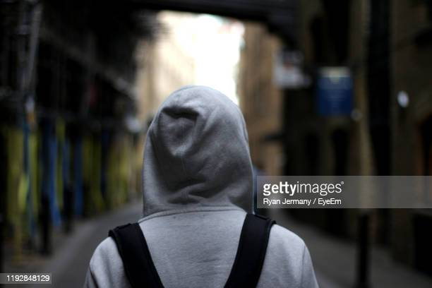 rear view of man in hood outdoors - hooded top stock pictures, royalty-free photos & images