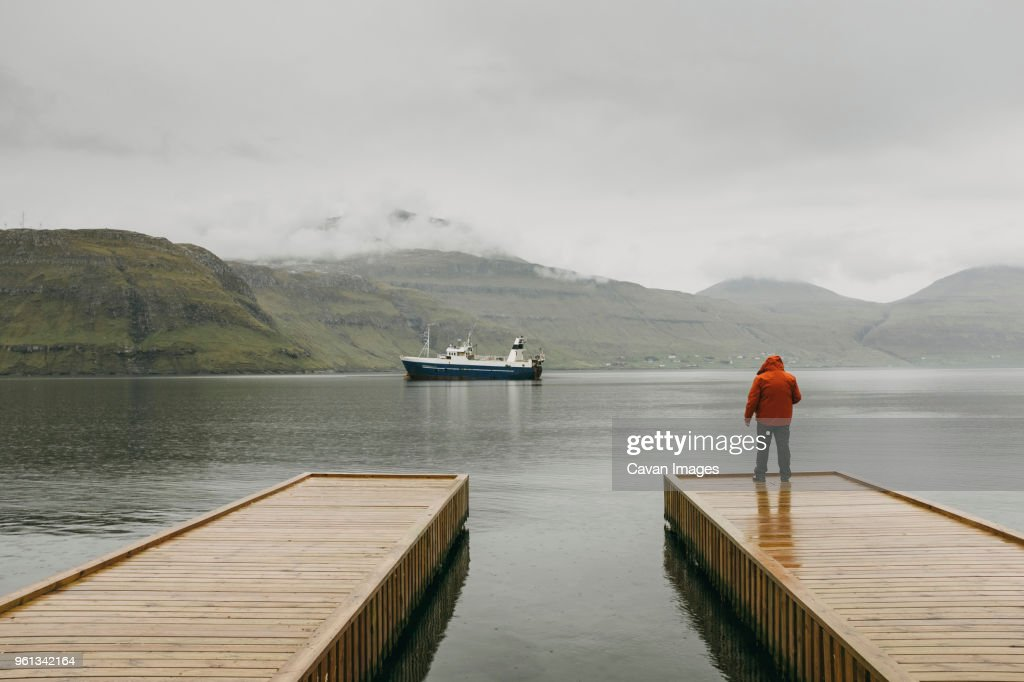 Rear view of man in hooded jacket standing on pier against mountains during foggy weather : Stock Photo