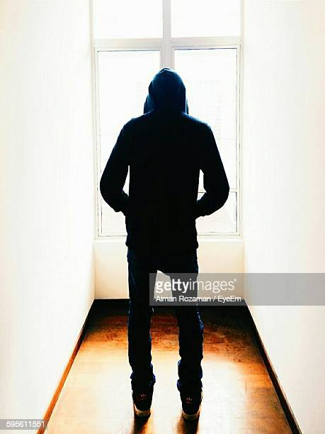 rear view of man in hooded shirt standing against window - capucha fotografías e imágenes de stock