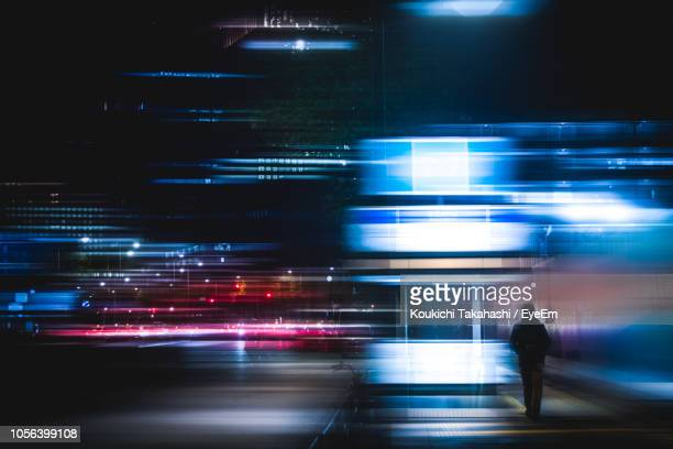 rear view of man in illuminated city at night - long exposure stock pictures, royalty-free photos & images