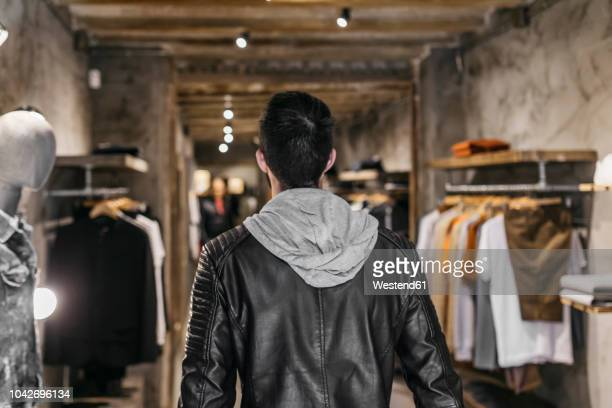 rear view of man in modern menswear shop - men fashion stock pictures, royalty-free photos & images