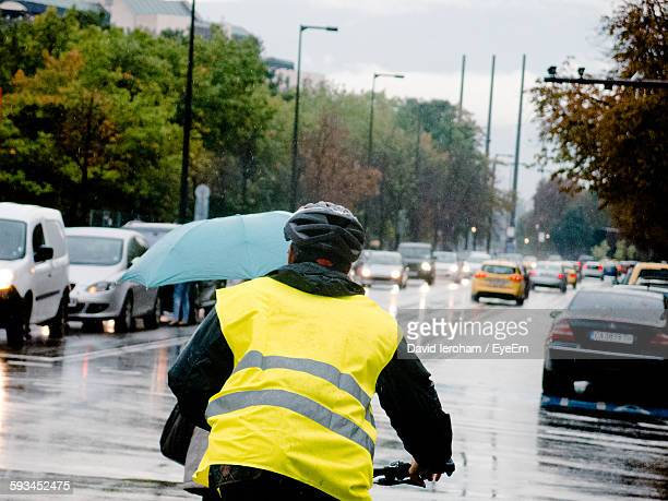 Rear View Of Man In Reflective Clothing Cycling On Wet City Street