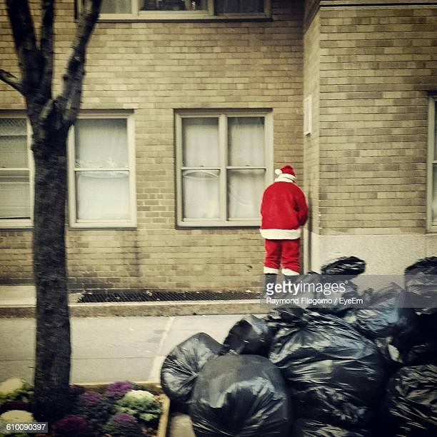 Rear View Of Man In Santa Claus Costume Standing Against Building