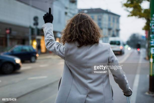 Rear view of man in the city hailing a taxi