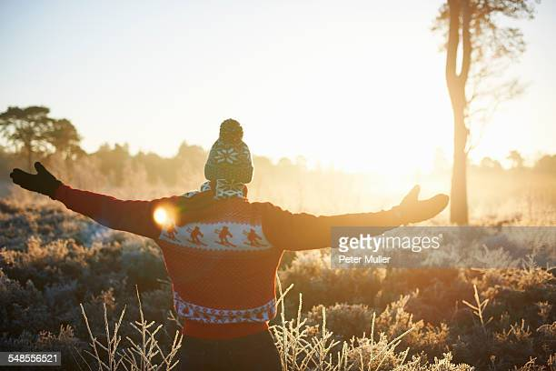Rear view of man in winter clothes with open arms in sunlight