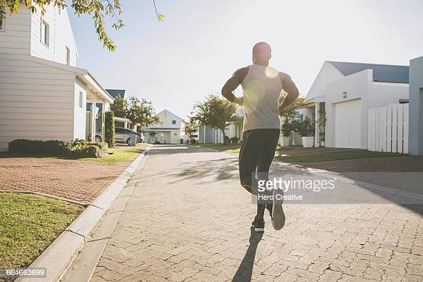 Rear view of man jogging in residential area