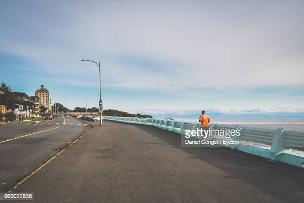 Rear View Of Man Jogging On Promenade Against Cloudy Sky