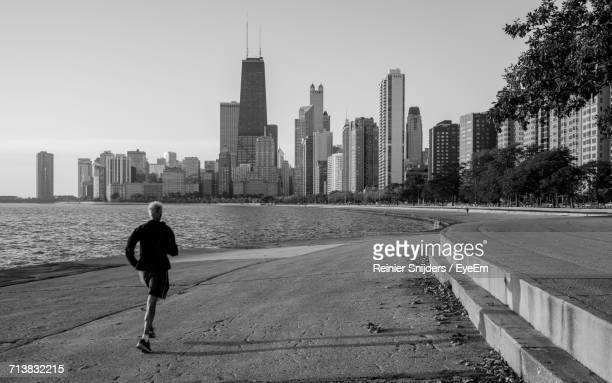 Rear View Of Man Jogging On Promenade Against Willis Tower In City