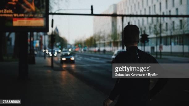Rear View Of Man Jogging On Street In City