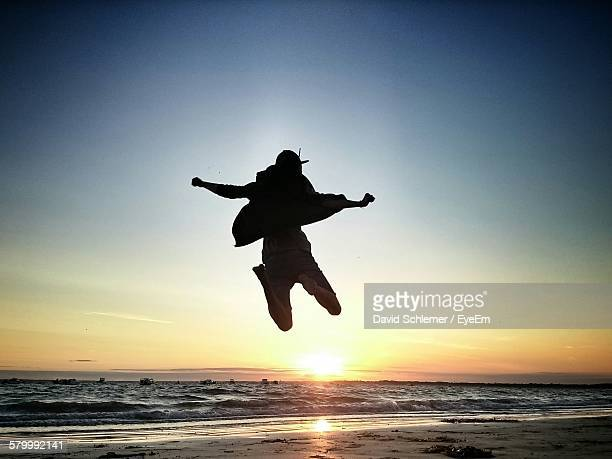 Rear View Of Man Jumping On Beach Against Sunset Sky
