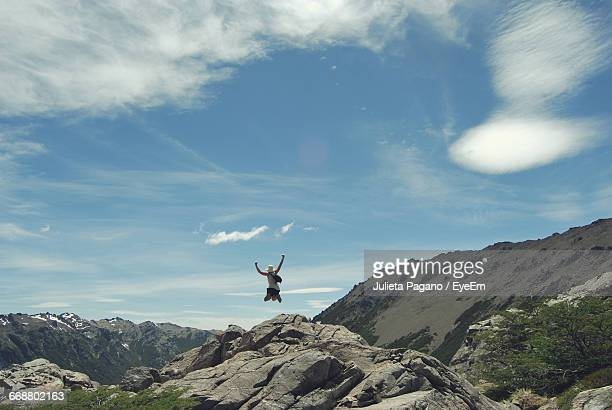 Rear View Of Man Jumping Over Rocks Against Sky