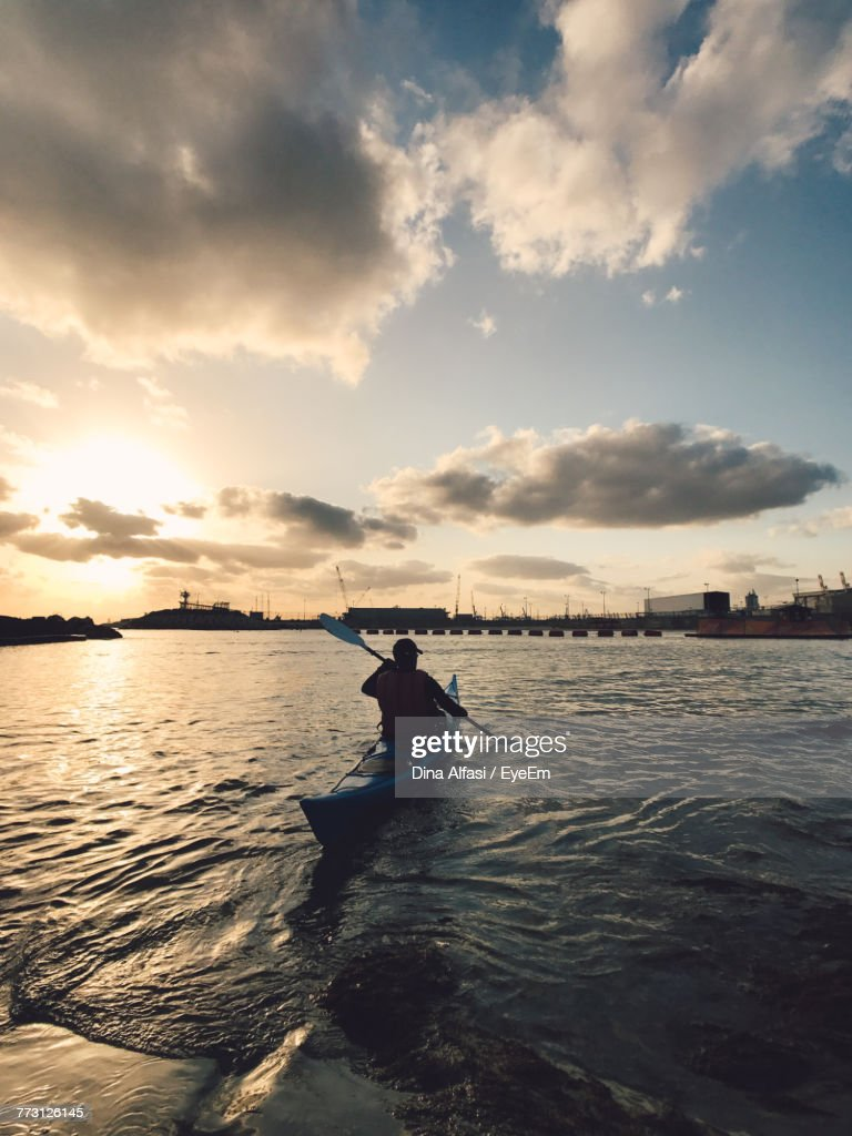 Rear View Of Man Kayaking On Sea Against Sky During Sunset : Photo