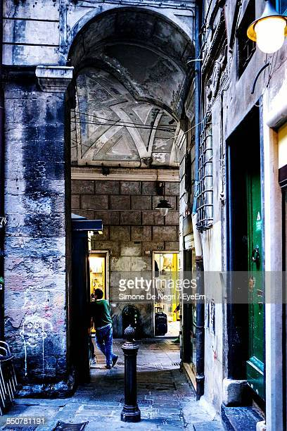 rear view of man leaning on building wall - centro storico foto e immagini stock