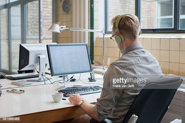 Rear view of man listening to headphones whilst working at office desk