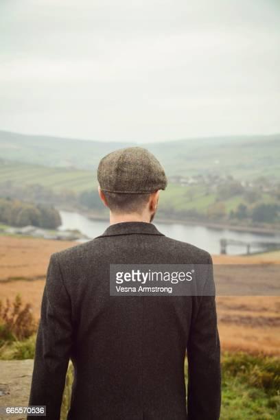rear view of man looking at a view - stausee stock-fotos und bilder