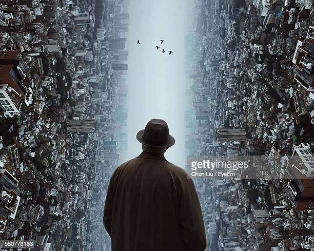 Rear View Of Man Looking At Birds Flying Amidst Cityscape Representing His Aspiration