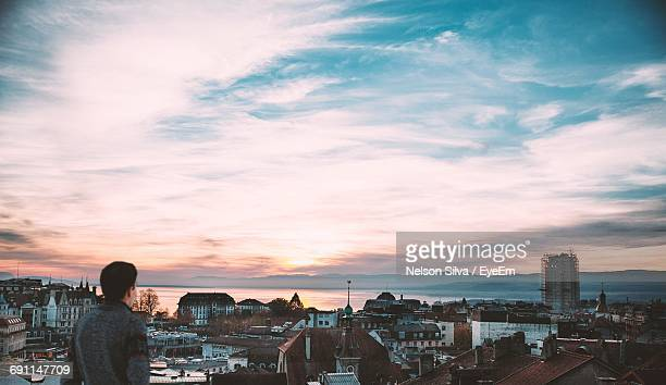 rear view of man looking at city by lake against sky during sunset - lausanne stock pictures, royalty-free photos & images