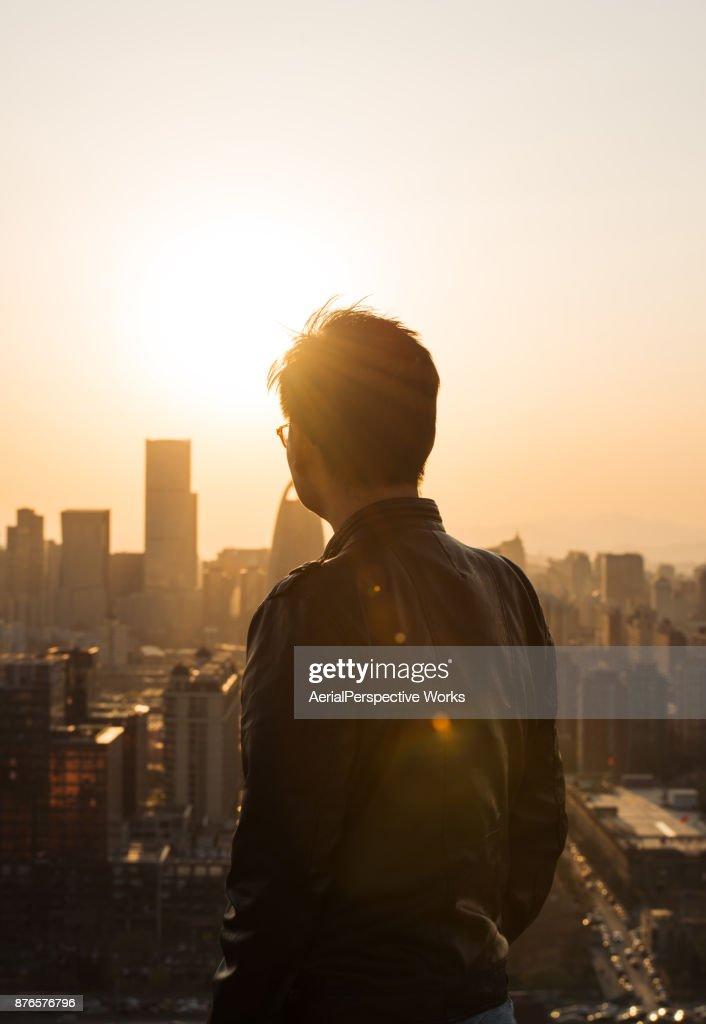 Vista traseira do homem olhando para a cidade da luz do sol : Foto de stock