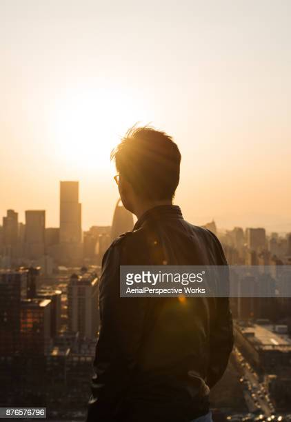 rear view of man looking at city in sunlight - back lit stock pictures, royalty-free photos & images