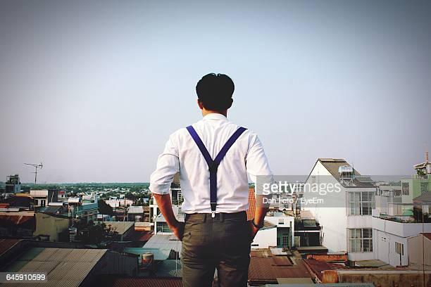 rear view of man looking at cityscape against clear sky - サスペンダー ストックフォトと画像