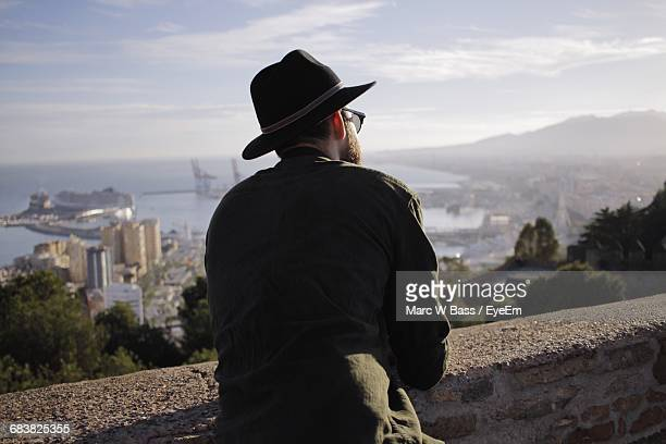rear view of man looking at cityscape and bay - wide brim stock pictures, royalty-free photos & images