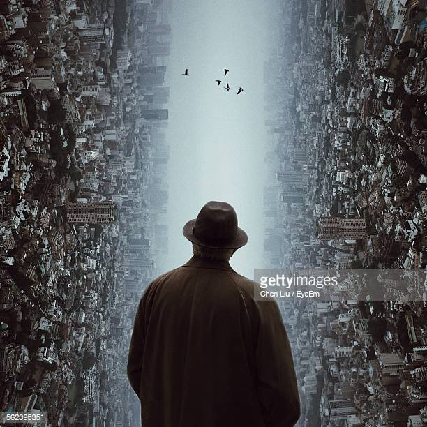 Rear View Of Man Looking At Flying Birds Between Crowded City