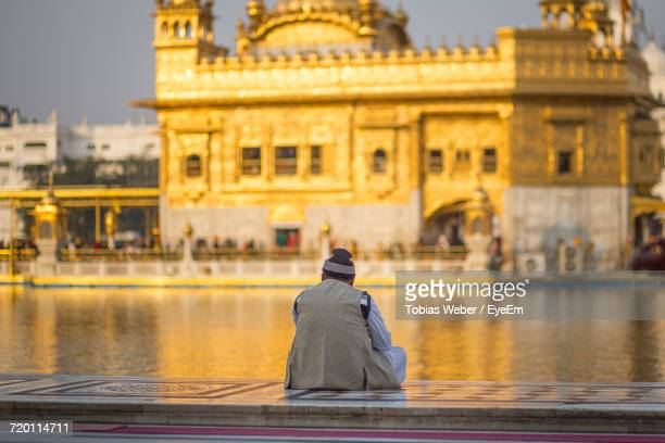 rear view of man looking at golden temple while sitting on retaining wall by pond - amritsar stock pictures, royalty-free photos & images