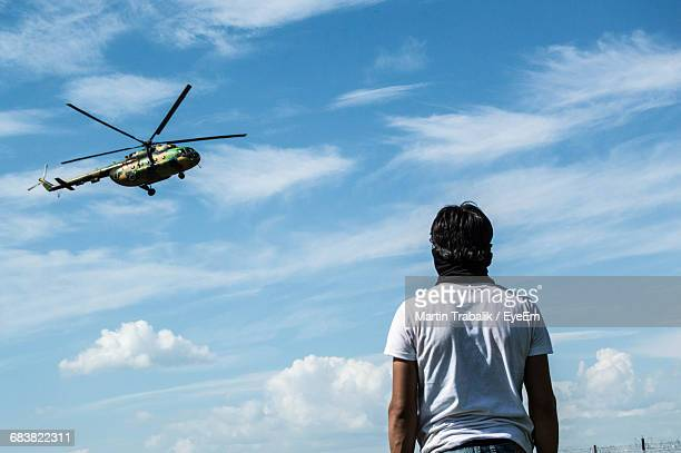 rear view of man looking at helicopter - humanitarian aid stock pictures, royalty-free photos & images