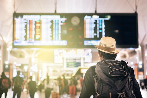 Rear View Of Man Looking At Illuminated Arrival Departure Board - gettyimageskorea