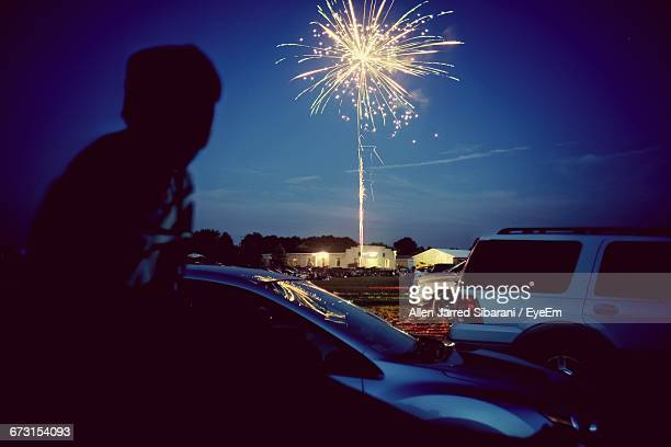 Rear View Of Man Looking At Illuminated Fireworks Against Sky At Dusk