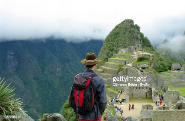 Rear View Of Man Looking At Machu Picchu Ruins On Mountain Against Sky