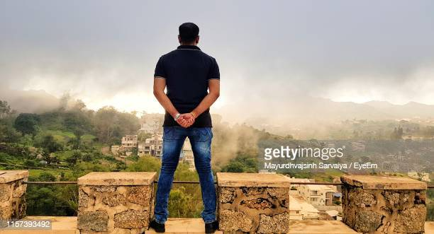rear view of man looking at mountains against sky - hands behind back stock pictures, royalty-free photos & images