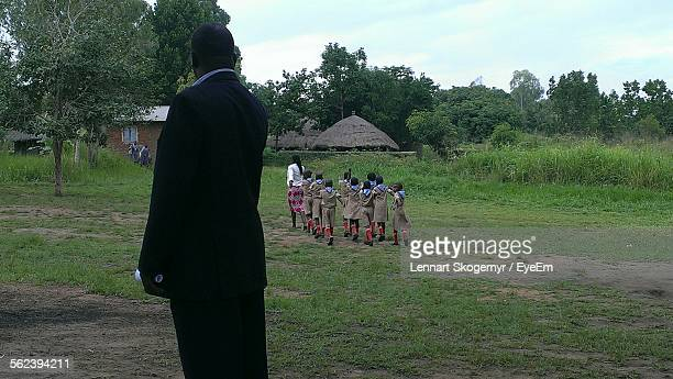rear view of man looking at school children marching - gulu stock photos and pictures