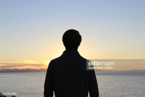 rear view of man looking at sea against sky during sunset - silhouet stockfoto's en -beelden