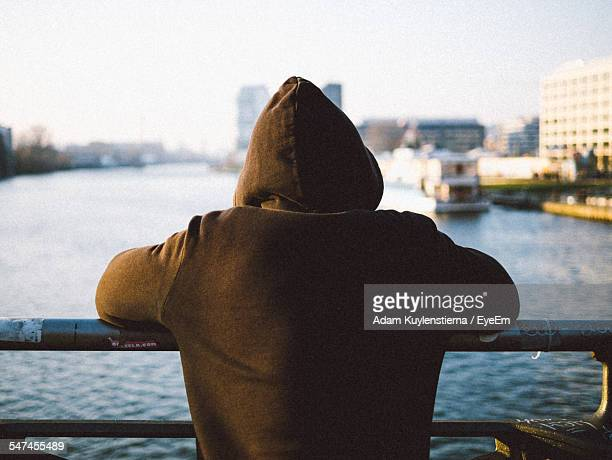 rear view of man looking at sea - hood clothing stock photos and pictures