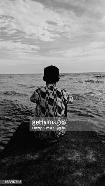 rear view of man looking at sea while sitting against sky - west kalimantan stock pictures, royalty-free photos & images