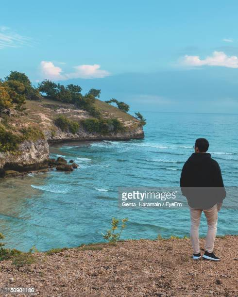 Rear View Of Man Looking At Sea While Standing On Beach Against Sky