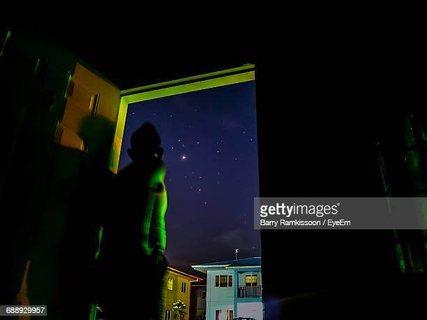 Rear View Of Man Looking At Star Field While Standing At Doorway At Night